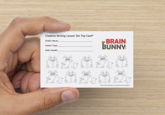 Picture of a hand holding a small card with the Brain Bunny Logo printed on it